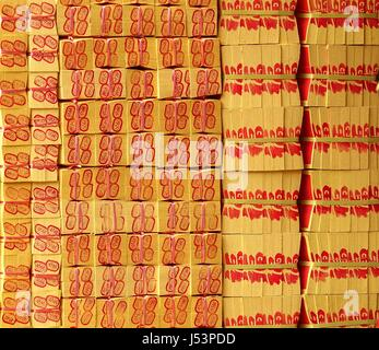 KAOHSIUNG, TAIWAN -- MARCH 16, 2014: A large stack of joss paper is prepared for burnt offerings at a local religious - Stock Photo