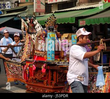 KAOHSIUNG, TAIWAN -- MARCH 16, 2014: Young men carry a sedan chair in which is seated the figure of a local deity - Stock Photo