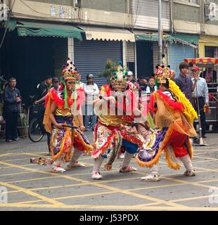 KAOHSIUNG, TAIWAN -- MARCH 16, 2014: Three young men with painted facial masks and dressed up as ancient warriors - Stock Photo