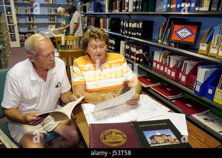 Arkansas Pocahontas Randolph County Library Genealogy Room woman man couple senior study read records census family - Stock Photo