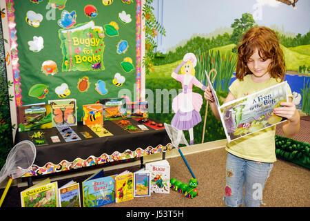 Arkansas Pocahontas Randolph County Library girl redhead elementary school reading children's books mural Little - Stock Photo