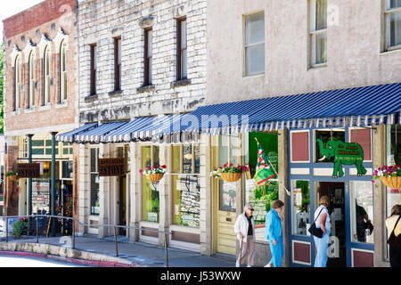 Arkansas Eureka Springs historic buildings renovated shopping woman women awnings specialty shops preservation facade - Stock Photo