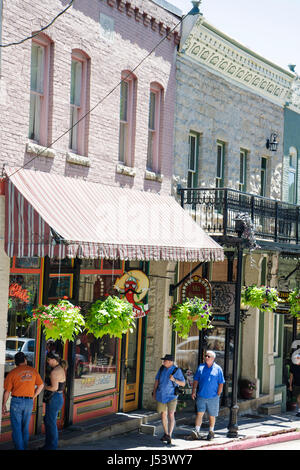 Arkansas Eureka Springs Spring Street historic building renovated awning shopping man woman couple specialty shops - Stock Photo