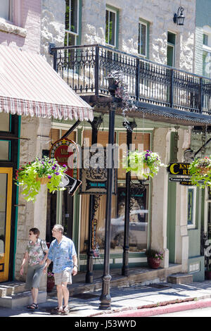 Arkansas Eureka Springs Spring Street historic building renovated shopping woman man couple wrought iron balcony - Stock Photo