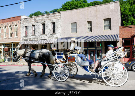 Arkansas Eureka Springs horse drawn carriage driver historic buildings renovated preservation facade stone - Stock Photo