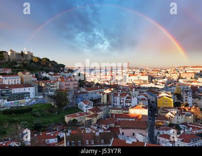 Rainbow over Lisbon, Portugal skyline with Sao Jorge Castle - Stock Photo