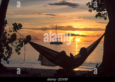 Beach vacations, silhouette of a woman reading in hammock at sunset on tropical island. - Stock Photo