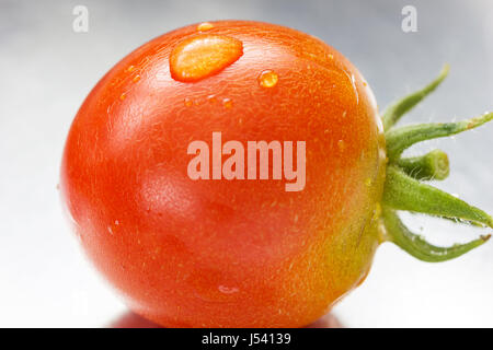 water pearl on red cherry tomato - Stock Photo