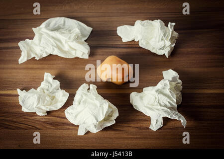 illn nose laying on wooden laminate encircled by handkerchiefs - Stock Photo