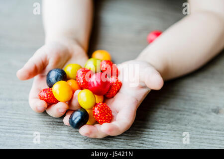 fruits in cute little child hands - kid - Stock Photo