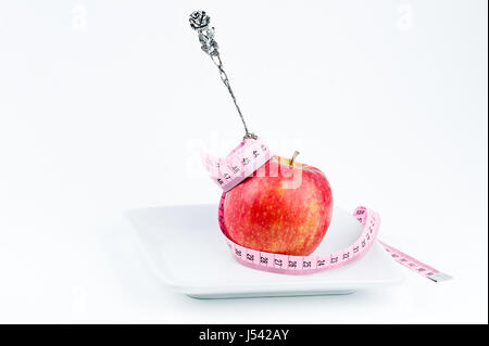 silver fork in apple on a plate with measuring tape, diet concept - Stock Photo