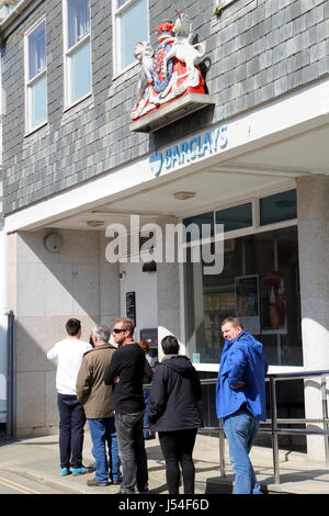 Padstow, Cornwall, UK - 6th April 2017: Bank customers queue for the ATM cash point outside Barclays Bank - Stock Photo
