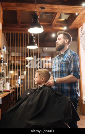 Delighted male barber standing behind his client - Stock Photo