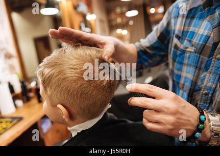 Nice pleasant barber combing the boys hair - Stock Photo