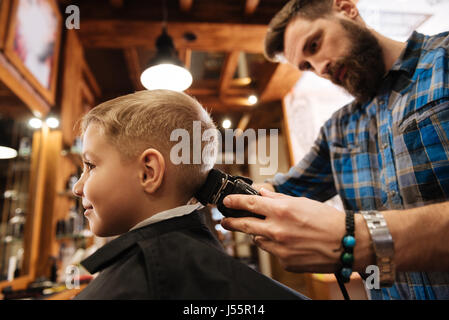 Nice bearded barber doing the haircut - Stock Photo