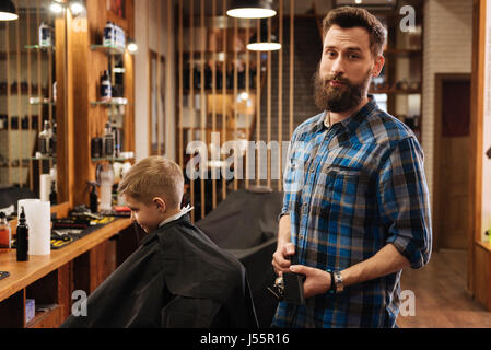 Nice good looking barber holding a comb - Stock Photo