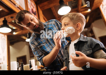 Nice good looking barber putting foam on the boys face - Stock Photo