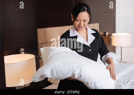 Positive hard working hotel maid looking at the pillow - Stock Photo