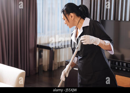 Nice hard working chamber maid looking at the floor - Stock Photo