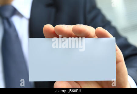 outstretched hand holding a blank business card - Stock Photo