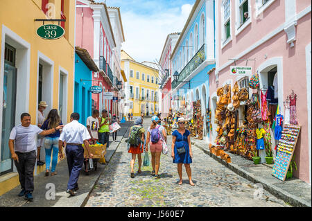 SALVADOR, BRAZIL - MARCH 9, 2017: Tourists walk past souvenir shops selling bags and local handicrafts line the - Stock Photo