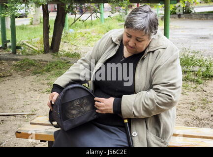 Volgograd, Russia. 17th May, 2017. A woman with a cat sits on a bench outside an apartment block at 60 Universitetsky - Stock Photo