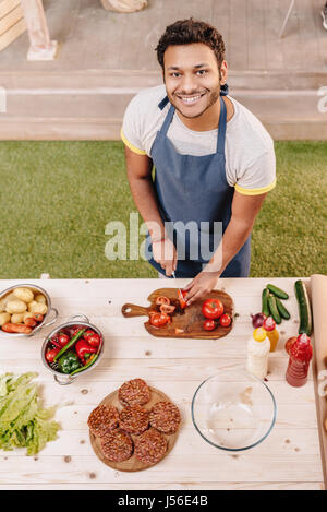 man making burgers and cutting red tomatoes outdoors