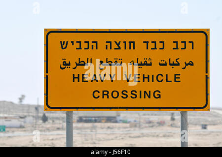 Heavy Vehicle Crossing warning sign in Hebrew Arabic and English - Stock Photo