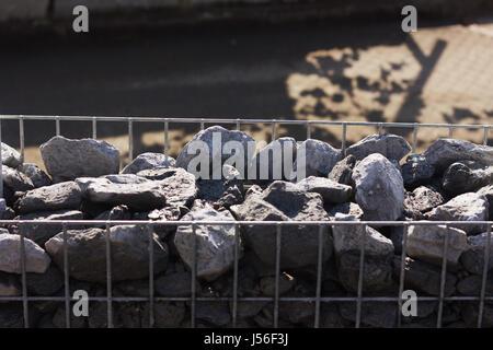 granite gravel into metal mesh. Gabione garden wall - Stock Photo