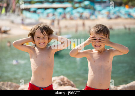 Two children on the beach, boys, playing and making funny faces, do not hear, do not see, enjoying their holiday - Stock Photo