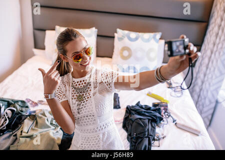 Female vlogger recording broadcast with digital camera. Woman taking a selfie video displaying fashion clothing and jewelery.