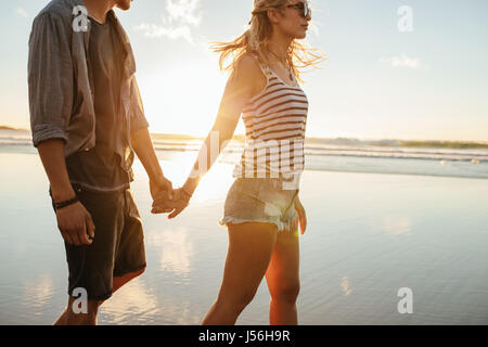 Young man and woman holding hands and walking on the beach on a sunny day. Couple on summer vacation walking on - Stock Photo