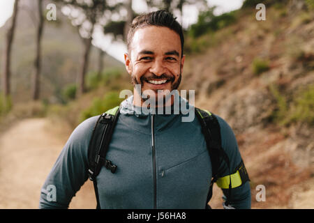 Portrait of healthy young caucasian man standing outdoors and smiling. Confident young male runner on country road. - Stock Photo