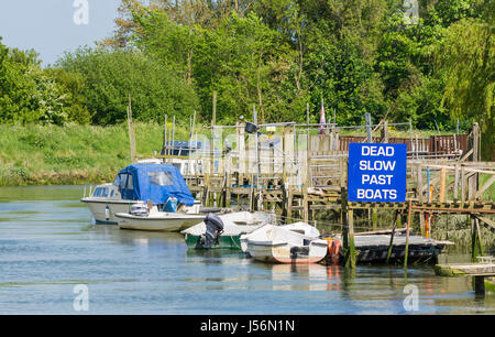 Dead Slow Past Boats sign next to moored boats on the River Arun in the countryside in Arundel, West Sussex, England, - Stock Photo