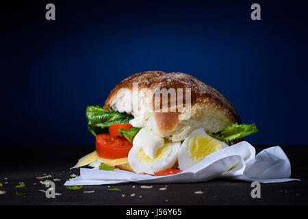 Delicious burger with egg, tomato, cheese, lettuce and mayonnaise on wooden counter. Copy space. - Stock Photo