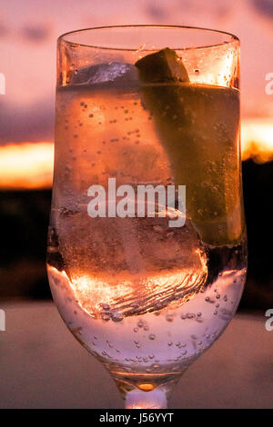 glass of drink with ice and lemon at sunset - Stock Photo