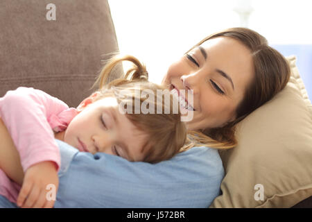 Close up of a proud mother watching her baby sleeping lying on a sofa in the living room at home - Stock Photo