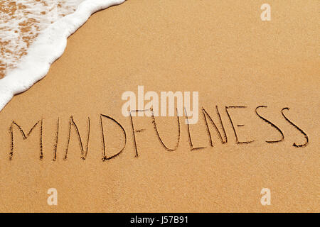 the word mindfulness written in the sand of a beach - Stock Photo