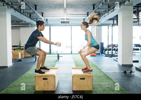 Young fit couple exercising in gym, doing box jumps. - Stock Photo