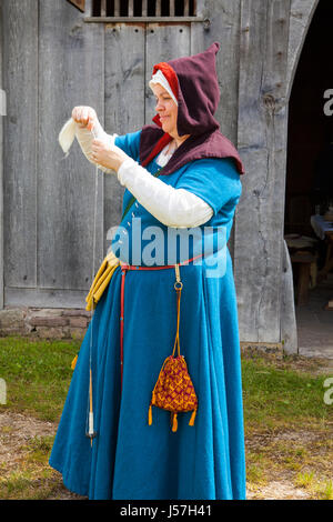 Spinning yarn by a member of a reenactment group, reconstructed medieval house, Nienover, Bodenfelde, Lower Saxony, - Stock Photo