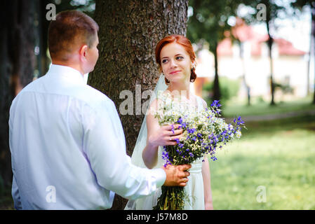 Bride and groom hold each other hands while they walk along the path in park - Stock Photo