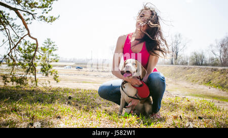 Young pet dog breeds beagle walking in the park outdoors. The girl carefully walks the puppy on a leash, plays and - Stock Photo