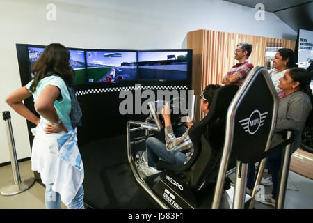 MUNICH, GERMANY - MAY 6, 2017 : People trying out the BMW car driving simulator in the BMW Welt exhibition center - Stock Photo
