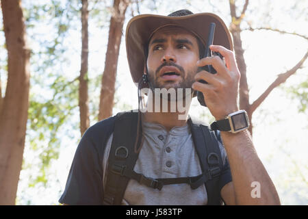 Man using walkie-talkie in the forest on a sunny day - Stock Photo