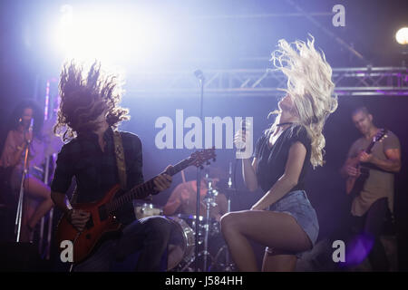 Female singer and male guitarist with tousled hair performing together on stage at nightclub - Stock Photo