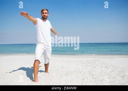 Man practicing warrior 2 pose while exercising at beach - Stock Photo