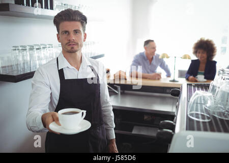 Portrait of waiter holding a cup of coffee at counter in restaurant - Stock Photo