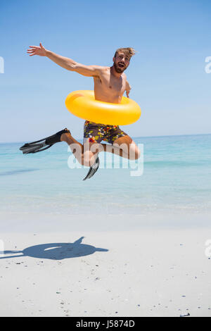 Playful man wearing inflatable ring jumping on shore at beach against clear sky - Stock Photo