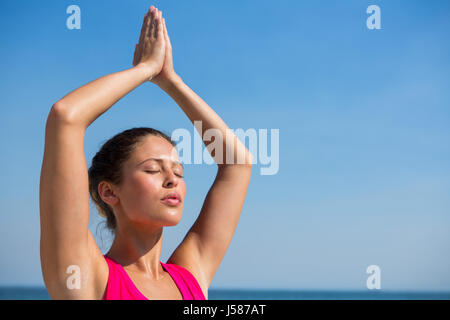 Young woman with eyes closed against clear sky exercising at beach - Stock Photo