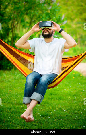 Young bearded man wearing virtual reality goggles relaxing in a garden hammock. Lifestyle VR fun and relax concept - Stock Photo